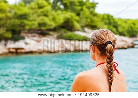 Young woman sitting and meditating on the beach