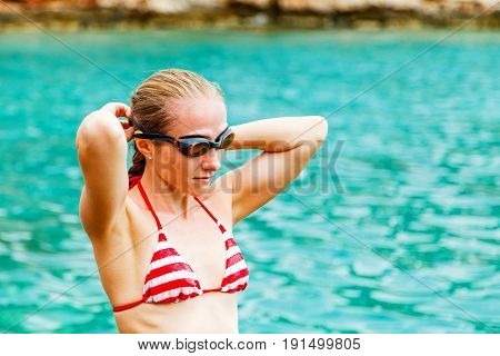 Photo of young woman in swimming goggles preparing to swim