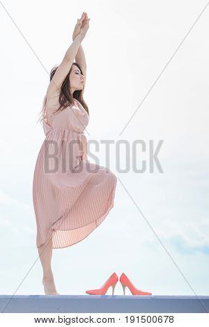 Fashionable clothing fashion and trends concept. Woman in long dress making dance posing barefoot high heels standing next to her.