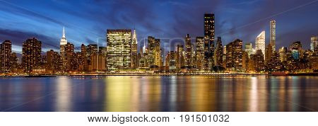 Panoramic view of Midtown East skyscrapers from the East River at twilight. Manhattan New York City