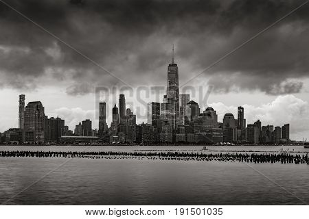 New York City Financial District skyline from across the Hudson River in Black and White. Low storm clouds over skyscrapers of Lower Manhattan