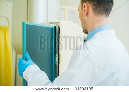 Caucasian X Ray Scanner Technician in His 30s Changing Radiographic Film in the Scanner.