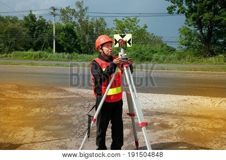 Surveyor or Engineer making measure by prism reflector on the highway.