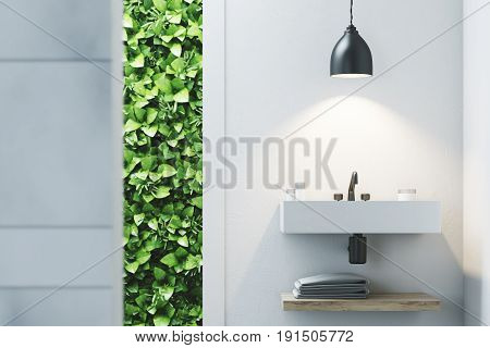 Eco bathroom interior with a narrow window green shrubbery is seen through it. There is a sink hanging on a marble wall. 3d rendering mock up