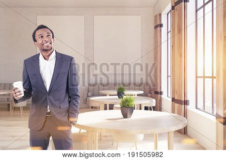 African American man in a modern cafe with two vertical posters on a concrete wall wooden floor round tables and chairs and beige sofas near tall windows. 3d rendering mock up toned image