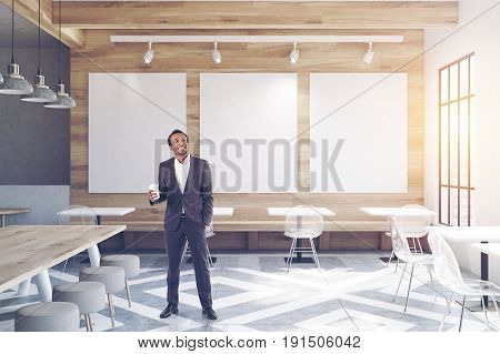 African American man in a modern cafe interior with wooden walls and gray floor pattern tables and round chairs near tall windows. Posters on the wall. 3d rendering mock up toned image