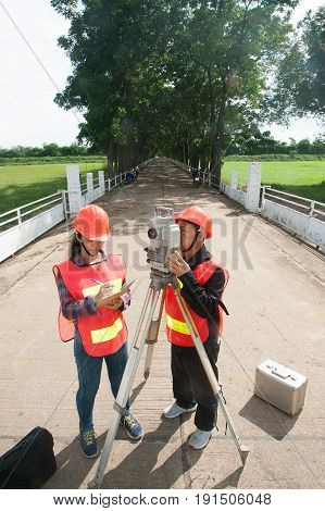 Surveyor or Engineer making measure with partner by Theodolite on the field.