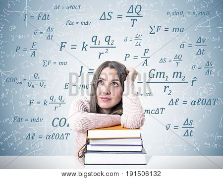 Portrait of a young woman wearing a pink sweater and sitting at a white table with a pile of colorful book. She is dreaming near a gray wall with different formulas written on it. Mock up