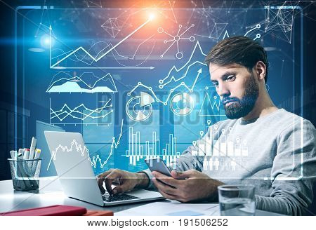 Portrait of a young bearded businessman in a sweater looking at his smartphone sitting in an office with graphs in the background. Toned image double exposure