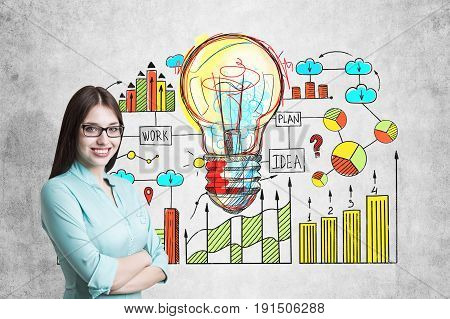 Young businesswoman wearing glasses and a blueish shirt standing with crossed arms and smiling while looking at the viewer. Good idea sktech on concrete