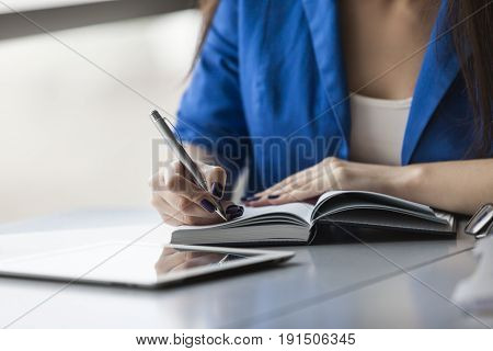 Close up of an unrecognizable businesswoman holding a planner and pen and sitting at her desk ready to take notes. There is a tablet on the table