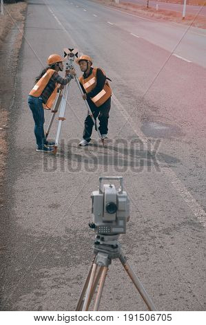 Surveyor or Engineer making measure with partner by Theodolite ans prism reflector on the highway.