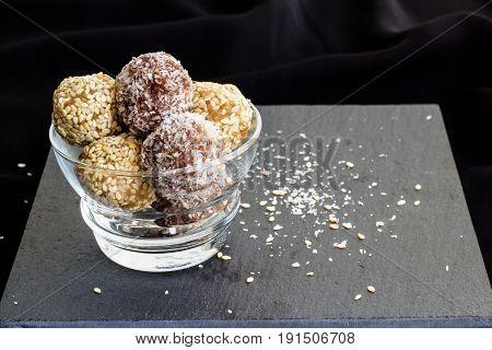 Homemade healthy paleo dates and chocolate energy balls. Vegan truffles. Copy space. Dark photo