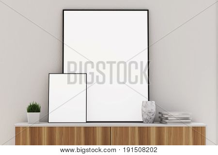 Front view of two vertical framed posters of different sizes standing on a wooden dresser in a room with gray walls. 3d rendering mock up