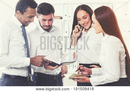 Two women and two men are standing together in an office. One of them is holding a notebook. Brainstorming. Team work. Toned image