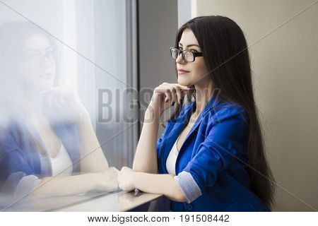 Portrait of a pondering businesswoman in glasses standing in an office lobby near a window sill and contemplating.