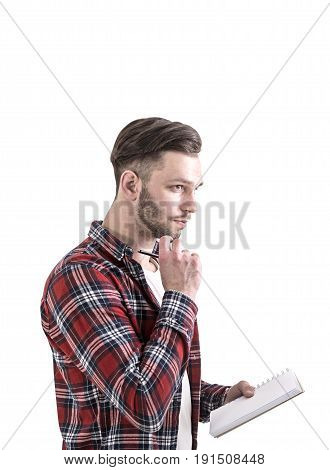 Side view of a bearded young man in a checkered shirt and a white T shirt holding a notebook and a pen and thinking. Isolated portrait.