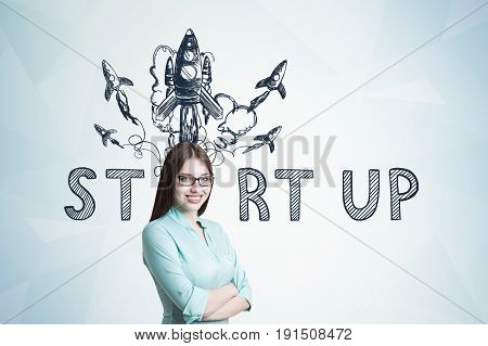 Young businesswoman wearing glasses and a blueish shirt standing with crossed arms and smiling while looking at the viewer. Gray wall start up rocket sketch