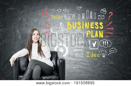 Young businesswoman with fair hair smiling and sitting in a leather armchair and talking on her smartphone. Blackboard with a business plan sketch