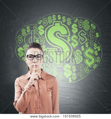 Close up of a young European woman with brown hair making a hush sign. Blackboard with a green dollar sign cloud on it