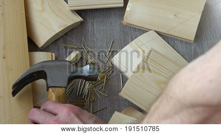 composition of boards, nails and hammer, the hand takes the hammer out of the frame.