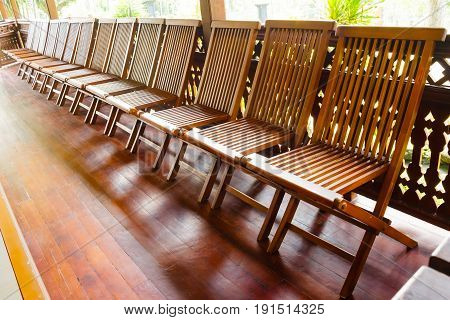 Empty wooden folding chairs are arranged sideways on the wooden floor. The chairs are brown colored.