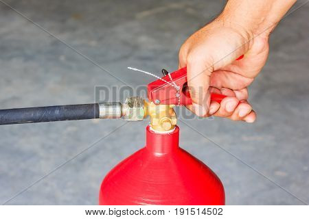 Male hands presses the trigger fire extinguisher Closeup