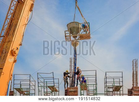 Construction workers working on scaffolding at a high level by the standards set must include a safety belt for safety. Heavy industry And Safety at Work concept.
