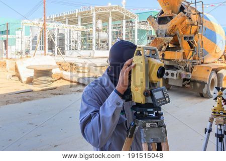 Surveyor worker making measuring with theodolite equipment at construction site.