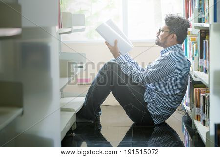 Men read and research book in the library.