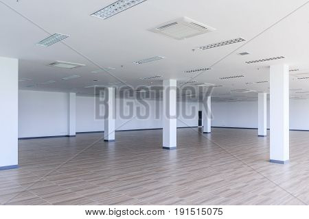 Pillar in empty big room interior with beige wooden laminate floor and painted walls Architecture concept