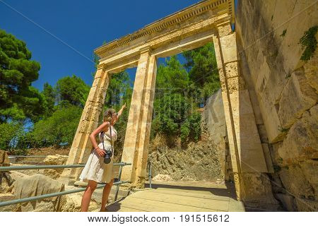 Traveler woman photographer shows the parodies, a monumental gate entrance of Ancient Theatre Epidaurus in Peloponnese, Greece, Europe. Epidaurus amphitheater is Archaeological Site Unesco Heritage.