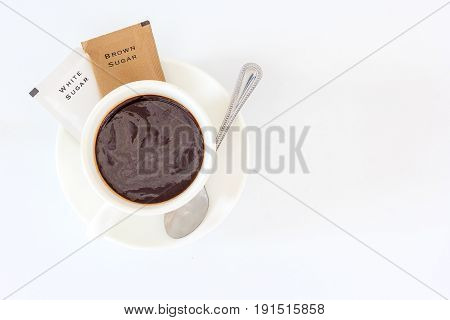 A cup of black coffee and sugar sachet for refreshing in the morning Top view with copy space and text.