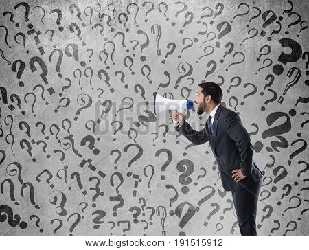 Businessman shouting on megaphone with question marks on wall