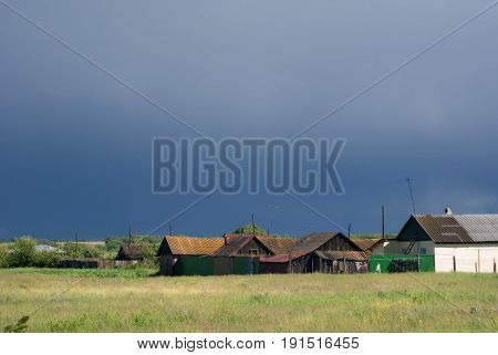 Russian village street in a gloomy cloudy sky.