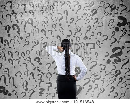 Rear view of confused businesswoman with question marks on wall