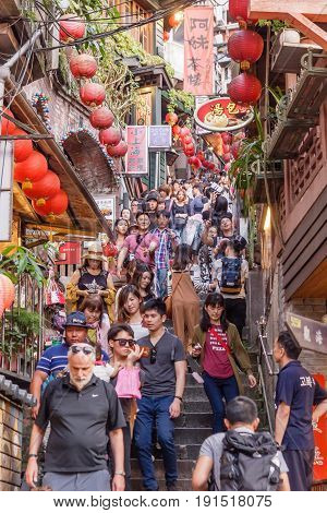 JIUFEN, TAIWAN - APRIL 30, 2017: Tourists walk down famed steps in Jiufen. A gold mining town developed under Japanese rule the city now attracts visitors for its nostalgic scenery.
