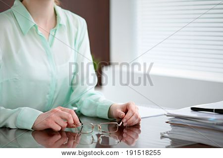 Business woman hands in a green blouse sitting at the desk in the office and holding glasses, the right window . She is thinking about the business problems, the successes, the concepts.