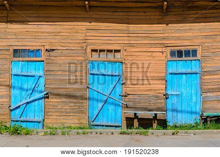 Old blue doors on wooden facade. Wood background