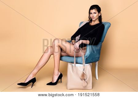 portrait of beautiful young woman in black bodysuit with stylish feminine bag posing in studio
