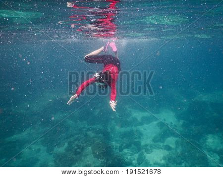 young asia woman wearing red shirt and dive goggle. she diving snorkeling under sea. this image for natureseascapeactivitytravel and people concept