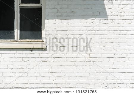 A white brick wall facade with window