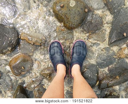 Asia Woman Wearing Shoes Standing On Beach With Small Stone And Have Small Wave Splashing To Foot Of