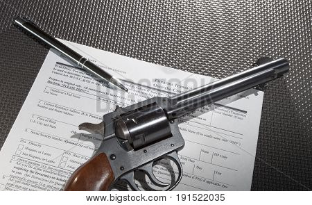 Pen with a revolver and background check paperwork underneath