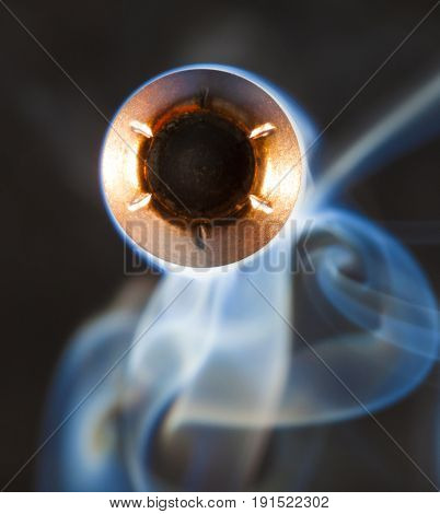Copper jacketed hollow point handgun bullet and smoke behind