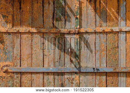 Old painted wooden garage door of brown color