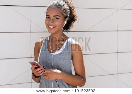 Beautiful sporty woman listening to music, looking at camera
