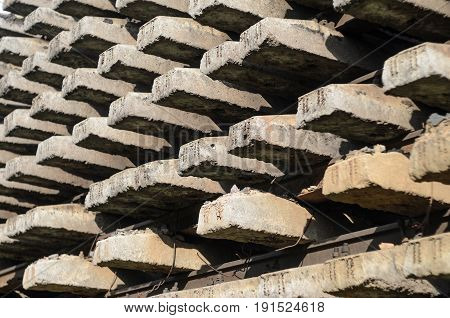 The rails and sleepers are stacked. Storage of railway infrastructure elements. Railway transport background.