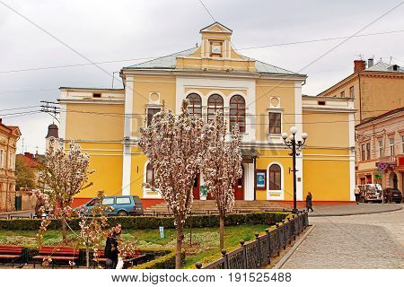 CHERNIVTSI, UKRAINE - APRIL 22, 2017: The view of Philharmonic hall from the Philharmonic square where tourists and locals like to feed the pigeons