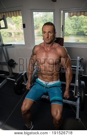 Muscular Man Exercising Trapezius On Machine